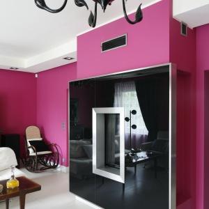 Intensywna fuksja na ścianach została przełamana czernią kominka ze srebrnymi obrzeżami. Oryginalny i pomysłowy kontrast połączony z kolorem żyrandoli.