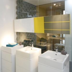 """Białe umywalki połączone z szafkami sprawiają wrażenie jakby wyrastały z podłogi. Jest to również nowoczesny element który dopełnia całość """"sypialnianej"""" łazienki."""