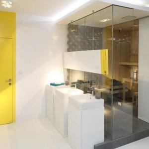 Drzwi wyjściowe swoją intensywnością żółtej barwy nadają otoczeniu świeży, słoneczny  oraz ciepły charakter wobec chłodnej bieli ścian i umywalek.