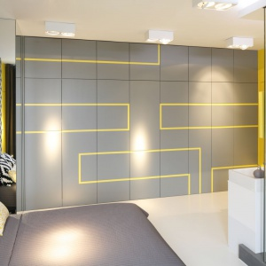 """Żółty """"labirynt"""" prowadzący przez szare ściany nadaje ostrości wnętrzu. Wyjściem z labiryntu są drzwi po przeciwległych stronach sypialni."""