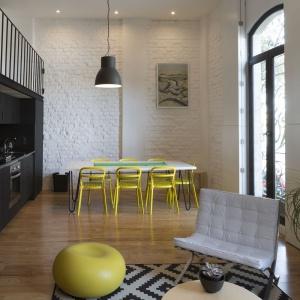 Do wnętrza, w którym panują klasyczna stonowane kolory, odrobinę radości i życia wprowadzają krzesła jadalniane i puf w salonie. Projekt: Eduardo Cadaval & Clara Solà-Morales. Fot. Miguel de Guzmán.
