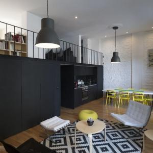 Strefa dzienna mieszkania to jadalnia, aneks kuchenny, pomysłowo scalony z antresolą oraz niewielki salonik. Wspólnym mianownikiem jest biała cegła na ścianie. Projekt: Eduardo Cadaval & Clara Solà-Morales. Fot. Miguel de Guzmán.