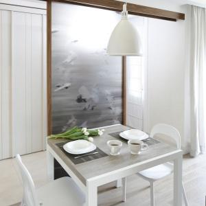 Biały stół, krzesła, a nawet lampa nad stołem - wszystko jest w eleganckim, śnieżnym kolorze. Projekt: Małgorzata Mazur. Fot. Bartosz Jarosz.