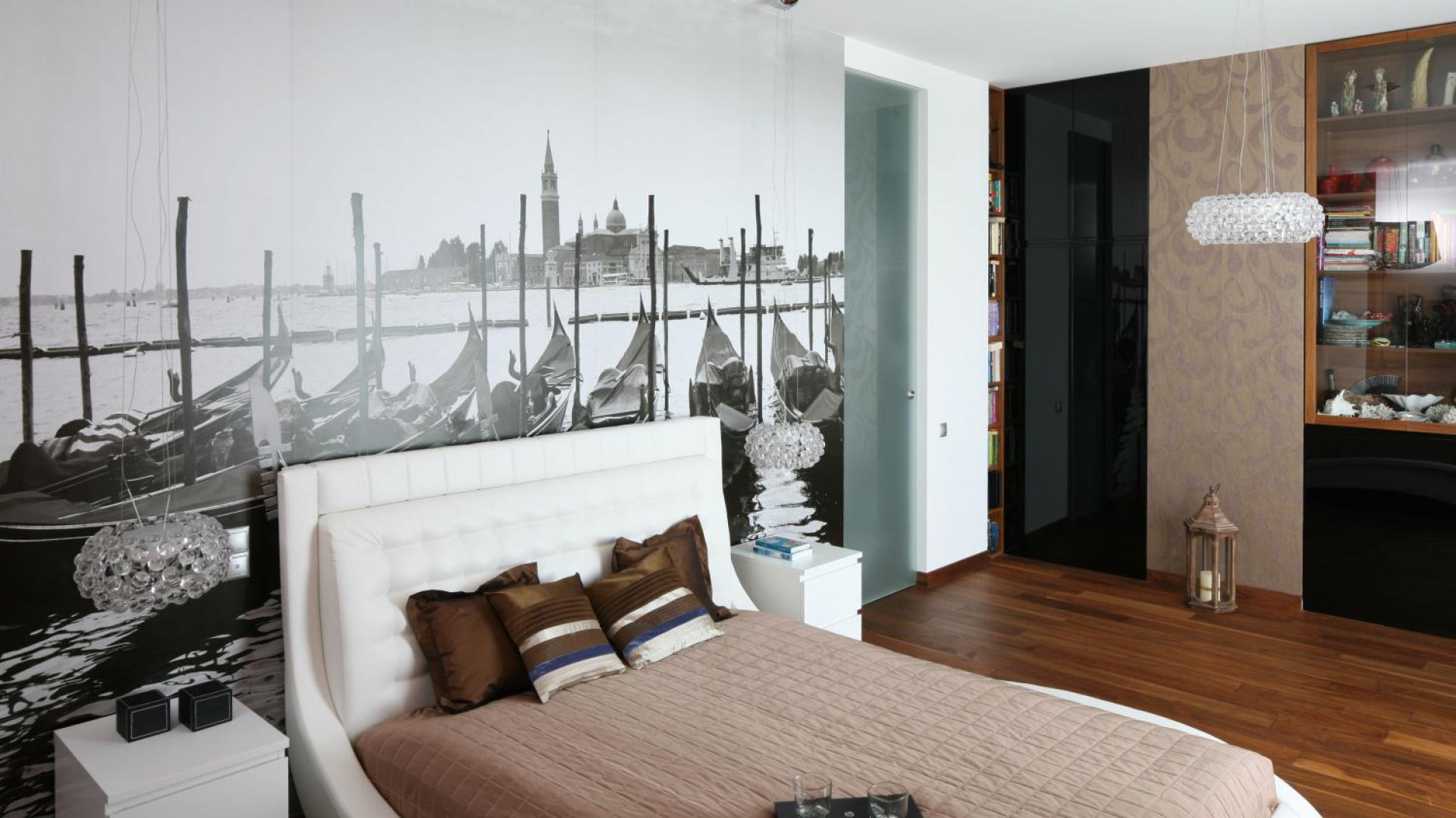 Główną dekoracja sypialni jest czarno-biała tapeta z widokiem na Plac św. Marka w Wenecji. Zdobi on całą ścianę za wezgłowiem łoża, które swa forma nawiązuje do gondoli weneckich ze zdjęcia. Projekt: Anna Maria Sokołowska. Fot. Bartosz Jarosz.