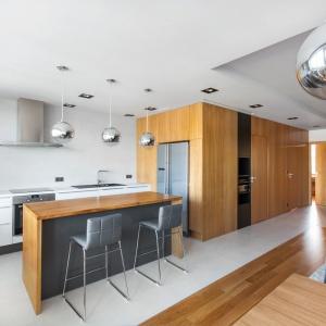 Wnętrze utrzymano w nowoczesnej stylistyce. Gładkie, minimalistyczne powierzchnie i wizualny porządek dekoracyjny sprawiają, że wnętrze zachwyca schludnością. Z kolei bogato zastosowane drewno ociepla wizualnie to mieszkanie. Projekt: mode:lina architekci. Fot. Marcin Ratajczak.