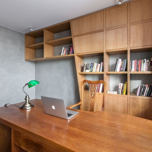 W gabinecie postawiono na podobne barwy, co w przestrzeni dziennej. Ścianę pokrywa szary tynk z efektem betonu, podłogę wyłożono drewnianą deską, a meble wykonane z drewna w tym samym kolorze. Projekt: mode:lina architekci. Fot. Marcin Ratajczak.