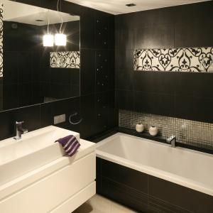 W tej łazience jest zarówno nowocześnie jak i stylowo. Proste, geometryczne formy korespondują z czernią i bielą okładzin. Proj. Małgorzata Galewska. Fot. Bartosz Jarosz.