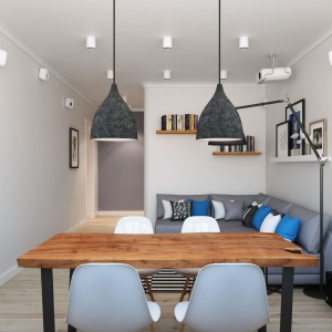 Drewniany stół wyróżniający się na tle chłodnego salonu to oryginalny i funkcjonalny dodatek, a duże, szare lampy pozwalają wykorzystać tą przestrzeń również do pracy. Projekt i wizualizacje: Alexei Ivanov i Pavel Gerasimov / Studio projektowe Geometrium.