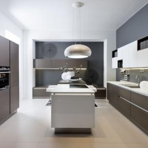 Fronty w kolorze czekoladowego drewna nadają wysokiej zabudowie w tej nowoczesnej kuchni bardzo elegancki, dystyngowany wyraz. Ożywia je biała wyspa w centrum pomieszczenia. Fot. Nolte Kuechen.