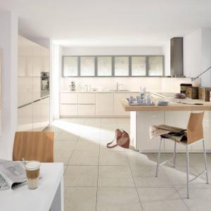 W tej jasnej, a zarazem przytulnej kuchni, zabudowa kuchenna chowa się w ścianie. Jej obecność zaznacza jedynie delikatnie różniący się od bieli ścian, kremowy kolor oraz wykończenie na wysoki połysk. Fot. Alno.