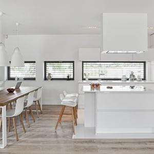 Całkowicie biała, nowoczesna kuchnia z zabudową, poprowadzoną na szerokość i wysokość całej ściany. Na pierwszy rzut oka, minimalistyczna zabudowa mogłaby całkowicie chować się w ścianie, gdyby nie sprzęt AGD w niej zamontowany. Fot. Atlas Kuchnie.