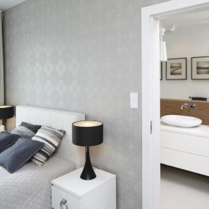 Sypialnia sąsiaduje z przytulną łazienką, w której prym wiedzie ciepły kolor drewna. Projekt: Małgorzata Galewska. Fot. Bartosz Jarosz.