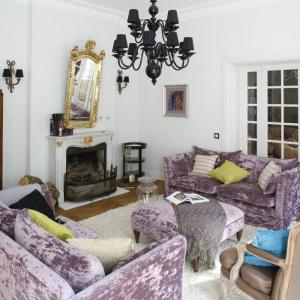 W dużym salonie stworzono dwie strefy wypoczynku. W pierwszej miejsce dla siebie znalazł zestaw wypoczynkowy w stylu angielskim, wykonany na zamówienie i obity angielskimi tkaninami. W drugiej strefie możemy odpocząć na odrestaurowanej sofce i fotelach w stylu Ludwika XVI, ustawionych wokół okrągłego stołu. Fot. Bartosz Jarosz.