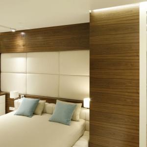 Sypialnię urządzono w złamanej bieli i ocieplono drewnem. Ścianę za wezgłowiem zdobi pikowana tapicerka z ekoskóry - ta sama, z której wykonano ramę łóżka. Projekt: Monika i Adam Bronikowscy. Fot. Bartosz Jarosz.
