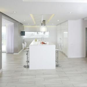 Kuchnia to królestwo sterylnej bieli, wykończonej na wysoki połysk. Zabudowa kuchenna pięknie wygląda w towarzystwie szarych ścian, pokrytych betonowym tynkiem. Projekt: Dominik Respondek. Fot. Bartosz Jarosz.