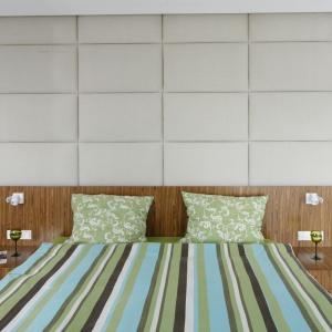 Duży pikowany zagłówek, pomimo nowoczesnego stylu, zapewnia sypialni przytulny charakter. Projekt: Dominik Respondek. Fot. Bartosz Jarosz.
