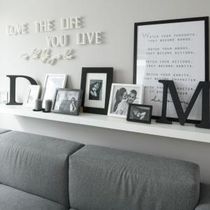 W salonie charakter wnętrza budują dodatki. Na półeczce nad sofą są to liczne ramki ze zdjęciami, grafikami i sentencjami oraz dekoracyjne napisy. Projekt: Karolina Łuczyńska. Fot. Bartosz Jarosz.