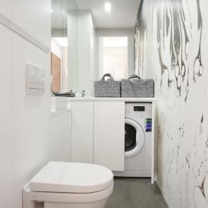 W mieszkaniu wygospodarowano również miejsce na toaletę z pralką - estetycznie schowaną za zabudową. W tym pomieszczeniu króluje biel. Projekt: Karolina Łuczyńska. Fot. Bartosz Jarosz.