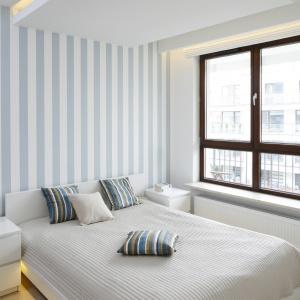 Pasy na ścianie optycznie powiększą sypialnię i sprawią, że pomieszczenie będzie wyglądało na wyższe. Projekt: Agnieszka Zaremba, Magdalena Kostrzewa-Świątek. Fot. Bartosz Jarosz.