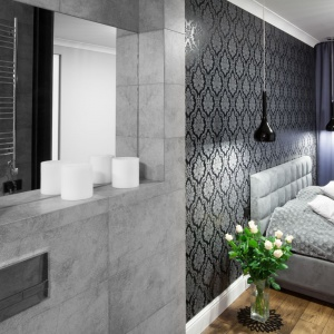 Ścianę nad łóżkiem zdobi elegancka tapeta, nadające sypialni powab i szyk. Projekt: Karolina Łuczyńska. Fot. Bartosz Jarosz.