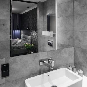 Z sypialni można bezpośrednio dostać się do łazienki, w której króluje szarość. Niewielką przestrzeń powiększa lustro o prostej formie. Projekt: Karolina Łuczyńska. Fot. Bartosz Jarosz.