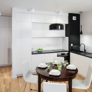 Biała kuchnia jest sercem tego wnętrza. Jej nowoczesna, minimalistyczna stylistyka pełni rolę tła dla zabytkowych mebli, które zgodnie z intencją właścicielki grają tutaj pierwsze skrzypce. Projekt: Ewa Para. Fot. Bartosz Jarosz.