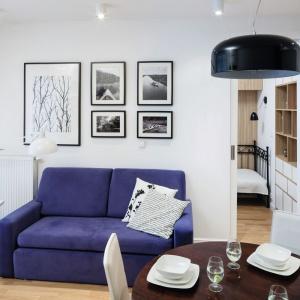 Niebieska sofa w pokoju dziennym stanowi mocny akcent we wnętrzu. Galeria zdjęć na ścianie to prywatna kronika ze spływów kajakowych, które są pasją właścicielki mieszkania. Projekt: Ewa Para. Fot. Bartosz Jarosz.