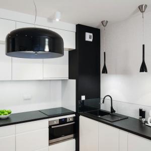 Kuchnia jest idealnie zgraną kompozycją bieli i czerni. Jej minimalistyczny styl miał tworzyć tło dla zabytkowych mebli w salonie. Projekt: Ewa Para. Fot. Bartosz Jarosz.