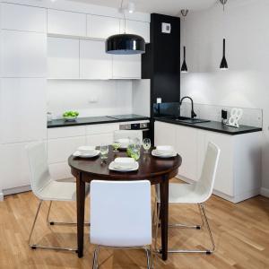 Wnętrze choć niewielkie, dzięki jasnym kolorom nabrało przestrzeni. Głównym bohaterem w salonie jest odrestaurowany kredens, który pięknie komponuje się z nowoczesnym wyposażeniem mieszkania. Projekt: Ewa Para. Fot. Bartosz Jarosz.