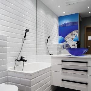 Fototapeta z widokiem Santorini została umieszczona na froncie szafki łazienkowej, której przestrzeń przeznaczono na pralkę oraz półki na ręczniki i kosmetyki. Projekt: Ewa Para. Fot. Bartosz Jarosz.