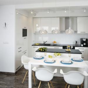 Mała jadalnia została urządzona pomiędzy kuchnią a salonem. Biały, połyskujący stół ustawiono wzdłuż wyspy kuchennej. Projekt: Katarzyna Uszok. Fot. Bartosz Jarosz.