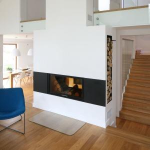 W przestronnym salonie zdecydowano się na dwustronny kominek o prostej acz niebanalnej stylistyce - dzięki temu rozwiązaniu płonący w nim ogień można podziwiać także z połączonej z kuchnią jadalni. Projekt: Małgorzata Galewska. Fot. Bartosz Jarosz.