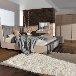 Sypialnia Romance to jasne kolory drewna połączone z elegancką, lekko połyskującą tkaniną na łóżku. Wysoki zagłówek może pełnić w sypialni rolę dekoracji. Fot. Paged.