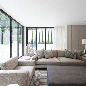 Właścicielom zależało na jasnym, przestronnym wnętrzu. Stąd w przestrzeni dziennej tradycyjne okna zastąpiły ogromne przeszklenia. Poza tym salon zaprojektowany został w ciepłych kolorach, które połączono z bielą ścian i firan. Projekt: Rupert Martineau, SHH Architects. Fot. Alastair Lever, Gareth Gardner.