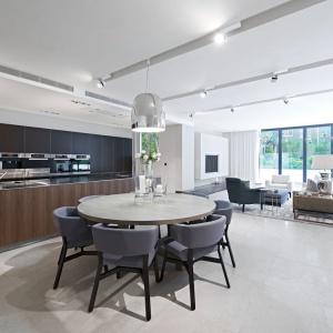 Jadalnię połączono z kuchnią. Dominują tu chłodne tony szarości i metalu. Jedynie fronty kuchennych szafek zostały ocieplone drewnem. Projekt: Rupert Martineau, SHH Architects. Fot. Alastair Lever, Gareth Gardner.