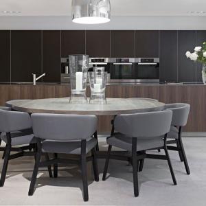 Okrągły stół w jadalni zapewnia komfortowe miejsce na rodzinne posiłki. Do ciemnego, drewnianego stołu dobrano miękkie, tapicerowane krzesła. Projekt: Rupert Martineau, SHH Architects. Fot. Alastair Lever, Gareth Gardner.