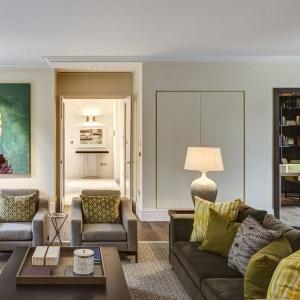 Strefa wypoczynkowa na piętrze ubrana została w kolory ziemi. Żółty połączony z zielenią stanowią oryginalne zestawienie z ciemną szarością mebli wypoczynkowych i jasnymi ścianami. Dopełnieniem ziemistych akcentów jest drewno. Projekt: Rupert Martineau, SHH Architects. Fot. Alastair Lever, Gareth Gardner.