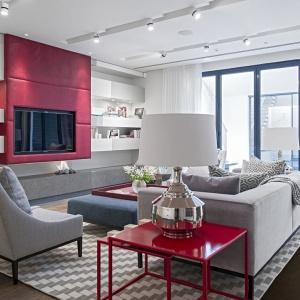 Kolejna strefa wypoczynkowa, tym razem na parterze domu, to już wnętrze nowoczesne. Szara kolorystyka mebli nawiązuje do białego koloru szafek i szuflad ukrytych w ścianie. Elementem, który nadał drapieżnego akcentu pomieszczeniu jest czerwony stolik oraz czerwone płyty okalające strefę TV. Projekt: Rupert Martineau, SHH Architects. Fot. Alastair Lever, Gareth Gardner.