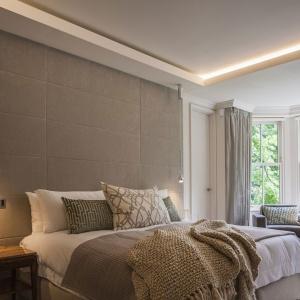 Sypialnia w ciepłych odcieniach cappucino. Jej przytulność podkreśla zarazem światło, które pochodzi z wiszących obok lamp, jak również światło LED z podwieszanego sufitu. Projekt: Rupert Martineau, SHH Architects. Fot. Alastair Lever, Gareth Gardner.