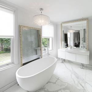 Łazienka jest duża i bardzo komfortowa. Wanna o opływowych kształtach idealnie nawiązuje do barokowej ramy luster. Projekt: Rupert Martineau, SHH Architects. Fot. Alastair Lever, Gareth Gardner.