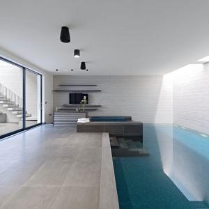 Basen umieszczony został na najniższej kondygnacji budynku. Dla większego komfortu użytkowników postanowiono umieścić tu również wyspę z barem. Projekt: Rupert Martineau, SHH Architects. Fot. Alastair Lever, Gareth Gardner.
