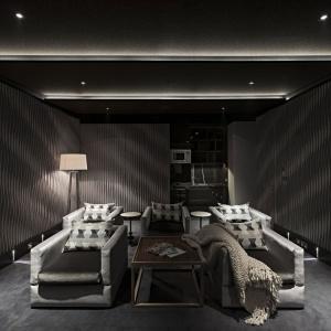 Szare fotele wypoczynkowe idealnie pasują do ciemnego wykończenia sali. Znalazło się tu również miejsce na drewniane stoliki kawowe w ciemnej i jasnej tonacji kolorystycznej. Projekt: Rupert Martineau, SHH Architects. Fot. Alastair Lever, Gareth Gardner.