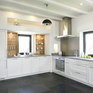 Kuchnia swoją przestronność i sielski charakter zawdzięcza białym frontom szafek oraz drewnianym półkom. Nie mogło zabraknąć detali w nowoczesnym stylu: metalicznego okapu oraz jasnoszarego blatu.