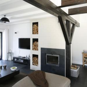 Ciekawym pomysłem stało się wyeksponowanie drewna do kominka poprzez wykucie specjalnych wnęk tuż obok niego. Warto tu zwrócić uwagę na względy ergonomiczne oraz dekoracyjne. Drewno doskonale łączy się również z ciemnym kolorem kominka oraz belek podsufitowych.