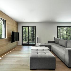W salonie drewno wiedzie prym: wchodząc w powierzchnie podłogi i jednej ze ścian. Reszta ścian jest pomalowana białą farbą, na tle której pięknie odznaczają się czarne ramy okien. Projekt: Projekt: YH2. Fot. Julien Perron-Gagné.