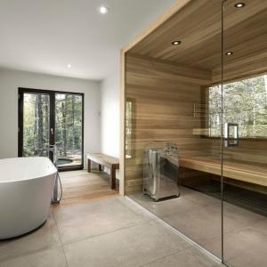 Łazienka, połączona z sauną to prawdziwe domowe centrum SPA. Wrażenie ekskluzywnego salonu kąpielowego potęguje wolno stojąca wanna i obecność drewna. Projekt: Projekt: YH2. Fot. Julien Perron-Gagné.