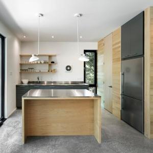 Dolną zabudowę kuchenną wykończono w eleganckim antracytowym kolorze, harmonizującym z częścią wysokiej zabudowy. W centrum pomieszczenia stanęła wyspa. Projekt: Projekt: YH2. Fot. Julien Perron-Gagné.