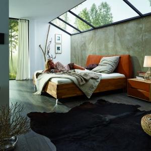 Łóżko Primavera łączy w sobie ciepło naturalnego drewna i przytulność tkaniny. Charakterystyczną cechą jest połączenie jasnej, orzechowej barwy drewna z soczystym kolorem pomarańczy na wezgłowiu. Fot. ADA.