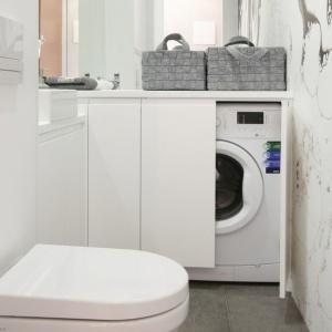 W małej białej łazience można zmieścić także pralkę - wystarczy praktyczny schowek. Projekt: Karolina Łuczyńska. Fot. Bartosz Jarosz.