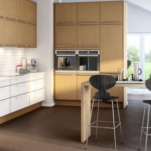 Górne szafki i wysoką zabudowę wykończono w drewnianym dekorze. Układające się pionowo słoje optycznie dodają pomieszczeniu wysokości. Dominację kolorów drewna przełamują białe fronty dolnych szafek. Fot. Marbodal.